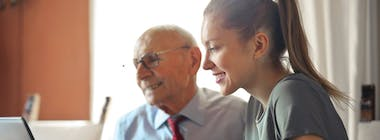 Elderly man and young lady at laptop holding bank card