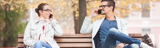 Couple sitting on park bench talking on phone