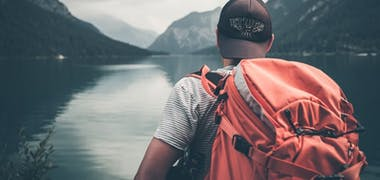 Man backpacking by a lake and mountains
