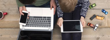 Family father and son using a laptop smartphone and tablet