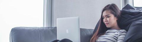 Woman sat on sofa using laptop