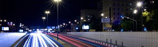 Dual carriageway in city at night with lights from cars