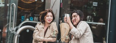 Two young women outside looking at a phone