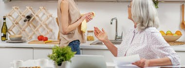 Mother and daughter in kitchen explaining bills
