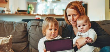 Mum with baby and toddler on sofa with ipad