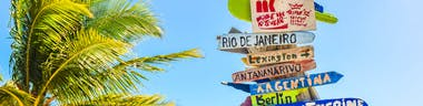 Sign with multiple destinations and a palm tree