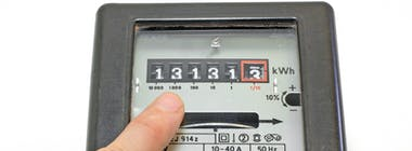 Dial electricity meter with hand pointing at reading