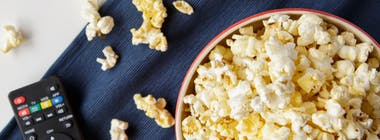 Bowl of popcorn and remote control on table
