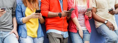 Group of young people standing against a wall using mobile phones