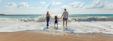 Family padding in the sea on a paradise beach