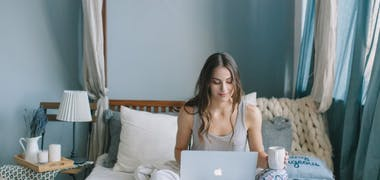 Woman sat on bed with laptop