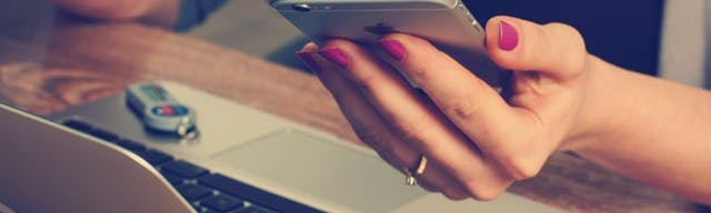 Woman holding mobile phone next to laptop